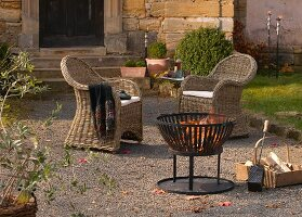 Two wicker armchairs and fire basket on Mediterranean terrace