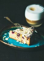 Dessert and coffee. Piece of lemon, ricotta, almond and raspberry gluten-free cake and glass of latte