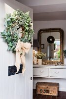 Wreath on open front door with view of gilt-framed mirror in hall