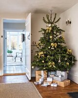 Presents wrapped in grey and brown under Christmas tree in hallway