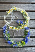 Two floral wreaths on wooden surface