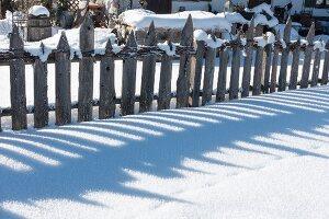 Wooden garden fence in snow