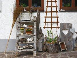 Leiter, Vogelkäfig, Korb, Besen und diverse Fundstücke als Deko vor Hauswand