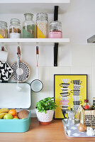 Various kitchen utensils and hand-painted storage jars on shelf
