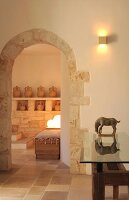Arched doorways and glass-topped table with wooden base in foyer of trullo