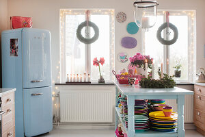 Colourful crockery on island counter and blue fridge in kitchen