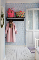 Brightly coloured baskets on coat rack mounted on blue and white diamond-patterned wallpaper