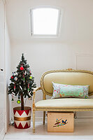 Christmas tree in colourful tub and Baroque couch below skylight