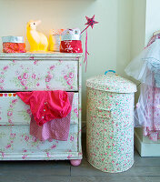 Revamped furnishings in child's bedroom: old chest of drawers and metal bin covered with floral wallpaper