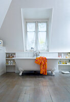Free-standing bathrub in white bedroom with dormer window