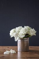 Posy of white roses in old silver pot