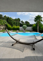 Hammock on curved stand in front of modern pool below palm trees