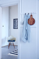 Towel and wooden board hung from pegs and classic chair in background