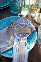 Small dreamcatcher and name tag on blue plate