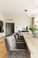 Rustikaler Holztisch mit eleganten Polsterstühlen in offenem Wohnraum