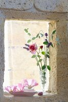 Delicate rose and lavender flowers in vase on windowsill