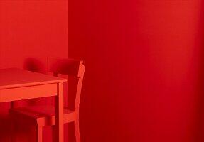 Roter Tisch und roter Stuhl vor roten Wänden