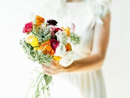 Woman holding bouquet of colourful ranunculus and cow parsley