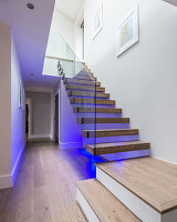 Floating staircase with indirect purple lighting