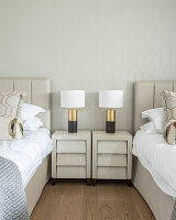 Lamps on two shiny bedside cabinets between twin beds
