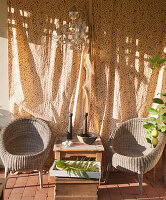 Two weathered wicker chairs in sunny seating area