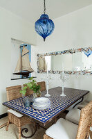 Mediterranean mosaic table and wicker chairs below large mirror on wall