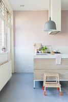 Stool with bright orange legs in modern kitchen in pastel shades