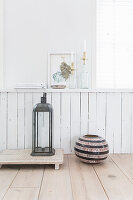 Lantern and vase on floor against white wainscoting with ornaments on ledge