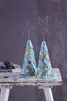 Stylised, conical Christmas trees covered in overlapping pieces of maps and decorated with messages of love and peace
