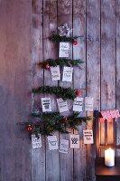 Weihnachtsbaum aus Tannenzweigen mit Weihnachtswünschen in verschiedenen Sprachen