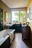 Bathtub, antique sideboard and sink in bathroom with large window and wooden floor