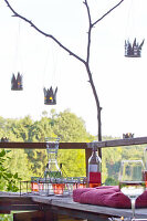 Candle lanterns hand-made from tin cans hung above benches on natural terrace