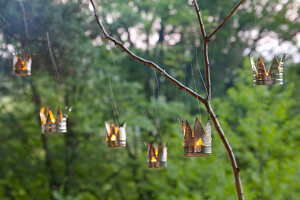 Candle lanterns hand-made from tin cans in garden