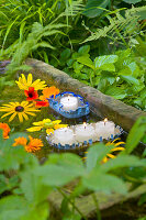 Fringed floating candle holders hand-made from sardine cans and flowers floating in sandstone trough