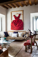 Red dress in wooden frame hung on wall above vintage metal couch