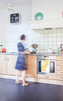 Woman in bright kitchen with wooden cabinets and dark floor