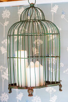 Three candles in suspended birdcage