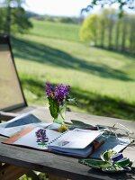 Gepresste Blume in einem Notizbuch auf dem Tisch mit Blick in die Natur