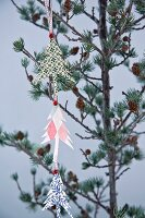 Garland of paper Christmas trees hung from larch branch