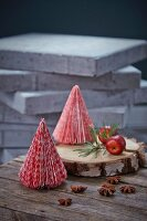 Small red and white paper Christmas trees on slice of tree trunk