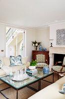 Couchtisch mit Glasplatte, Sofa, Antikkommode und Kamin im Wohnzimmer