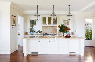 Mittelblock mit Marmor-Arbeitsplatte, darüber Pendelleuchten mit Glasschirm in offener Küche