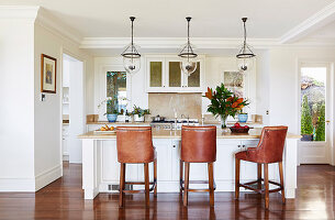 Leder-Barchocker am Mittelblock, darüber Pendelleuchten mit Glasschirm in offener Küche