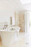 Badezimmer mit frei stehender Wanne, Duschkabine und Terrassenzugang