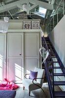 Schrank mit Kassettentüren neben violetter Treppe zum Dachgeschoss