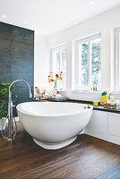 A designer bath tub in front of a window with a bench in a cosy bathroom