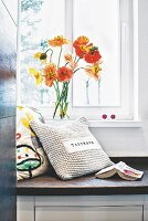 A decorative cushion and a bunch of flowers on a made-to-measure bench in front of a window in a bathroom