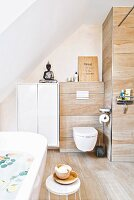 An attic bathroom with wood-style tiles