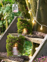 Candle lanterns wrapped in moss on steps next to tree