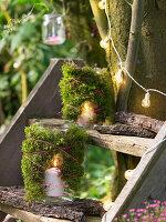 Mit Moos umkleidete Windlichter auf einer Treppe am Baum
